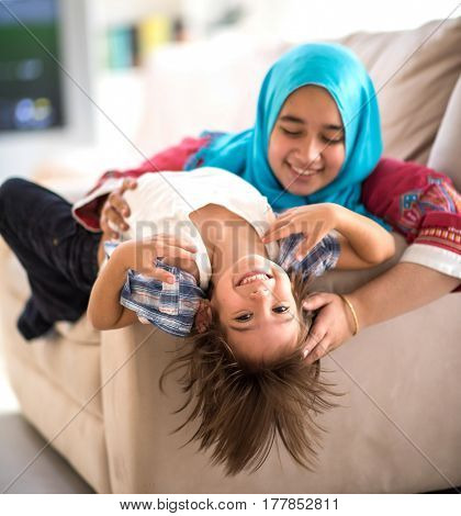 Muslim mother and cute little son with long hair on sofa playing together