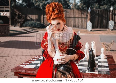 The Red Queen is playing chess. Red-haired gorgeous woman in a chic vintage dress. Fashion Photo. Gorgeous model. Play chess concept