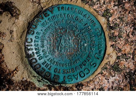 A geodetic survey marker at Acadia National Park near Bar Harbor Maine.