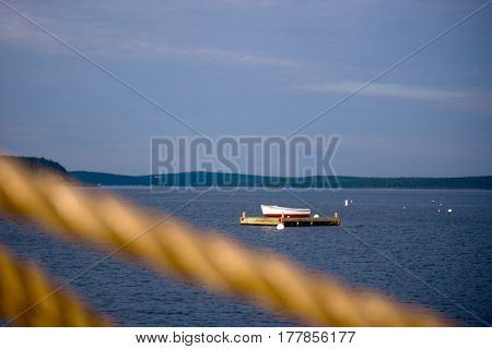 Small Rowboat On Dock In Ocean With Rope In Foreground