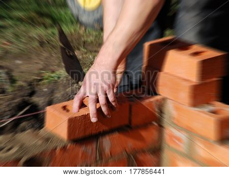 Construction worker laying bricks wall of building. Zoom effect centered of hand holding brick.
