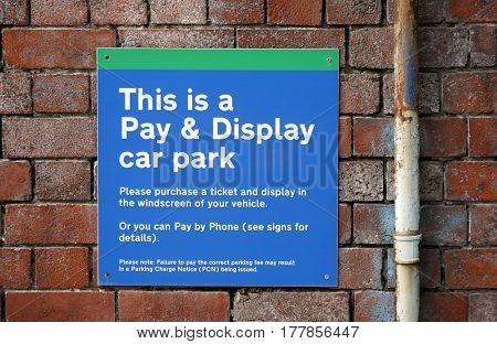 Closeup of city parking notice fastened to brick wall.