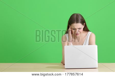 Beautiful young woman suffering from headache while working with laptop, on color background