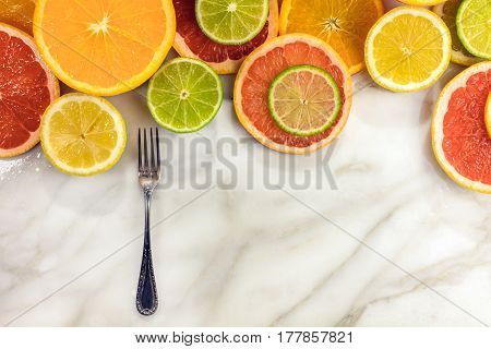 Vibrant juicy citrus fruits on a white marble texture with copy space. Grapefruit, lime, lemon, and orange slices with a little vintage fork