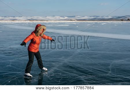 The girl learns to skate on the open ice. Strong wind blows. Ice is very beautiful, with cracks, and it's hard for a girl to resist it.