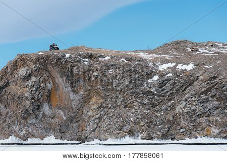Quad bike in winter on a rock. Beautiful minimalistic landscape. Rocky high bank with a cliff. The ATV stopped and laid the route.