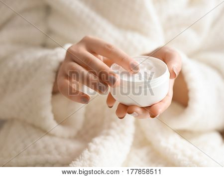 Beautiful young woman with jar of cream in spa salon, closeup
