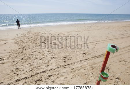 Angler fishing on the beach with rod stand on foreground. Sea angling sport at the beach Huelva Spain