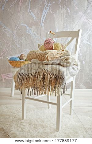 Basket with knitting yarn and knitwear on chair in the room