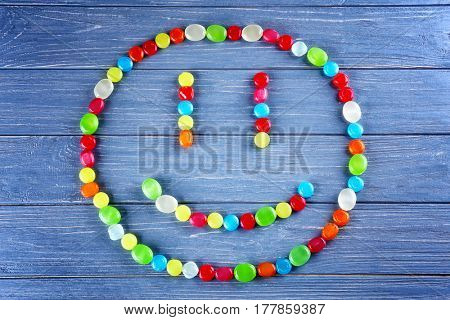 Different cough drops in face shape on wooden background