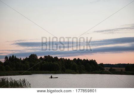 A fisherman in a boat floating on the lake and fishing. Evening landscape. Evening sky with clouds. The surface of the water