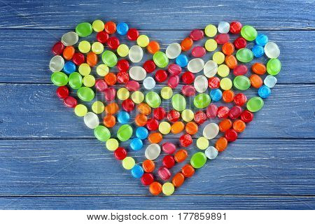 Different cough drops in heart shape on wooden background