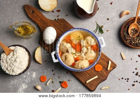 Portion of delicious chicken and dumplings in decorative soup pot on kitchen table