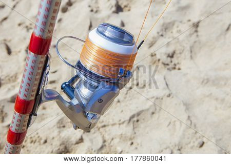 Fishing reel on rod detail with orange showy line for last line section Huelva Spain