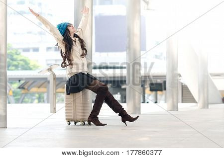 Woman Tourist Sitting On Suitcase And Hand Up With Happiness Moment.