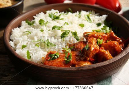 Delicious chicken tikka masala and rice in bowl, closeup