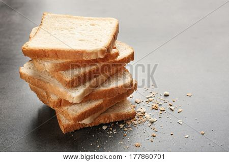 Slices and crumbs of wheaten bread on grey background
