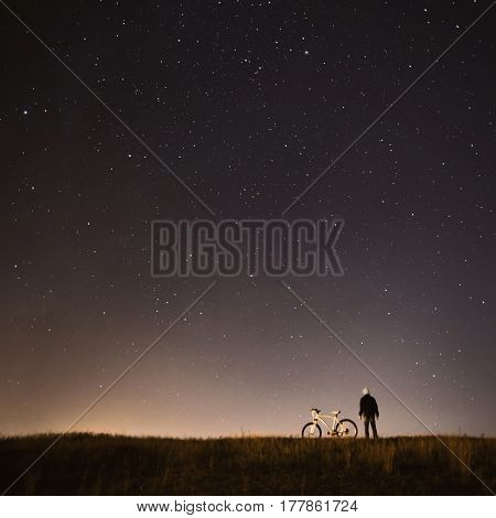 Dark silhouette. Starry sky night photography astrophotography the silhouette of a man a man standing next to a mountain bike on the background of a starry sky the white bicycle. Man silhouette