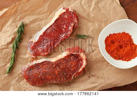 Raw steaks with spices and rosemary on parchment