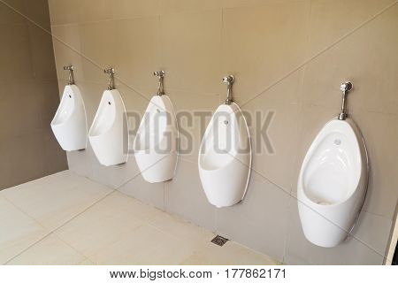 Urinals Bowl in public men's bathroom with Modern white ceramic design in the toilet WC.