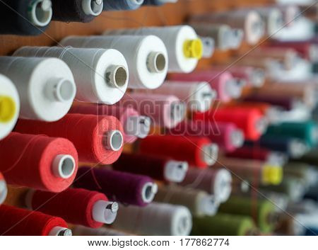 Spools with colorful threads on rack, closeup
