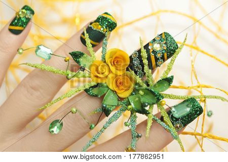 Nail design with acrylic yellow roses and leaves hand-female hand with sequins,rhinestones,beads on a white background closeup.Nail art.