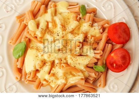 Portion of delicious pasta with cheese sauce on plate, closeup