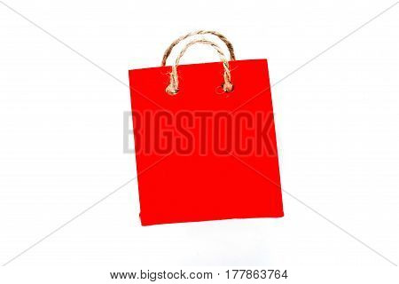 Tiny shopping bag of red paper with rope handles. Isolated over white