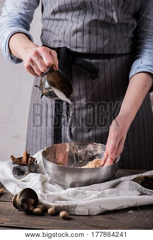 Human hands adding sugar to ingredients for making cookies in metal bowl, horizontal composition
