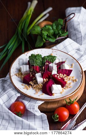 Healthy salad with beetroot, pearl barley, cilantro and brynza cheese on white plate over wooden board background, selective focus, vertical composition