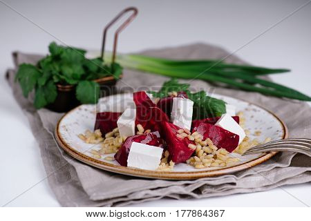 Healthy salad with beetroot, pearl barley, cilantro and brynza cheese on white plate over grey background, selective focus, horizontal composition