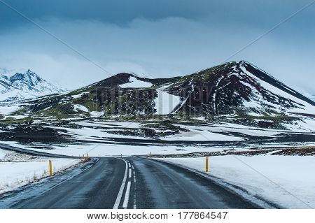 long road and snowcapped mountain Iceland main road