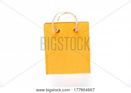 Tiny shopping bag of orange paper with rope handles. Isolated over white