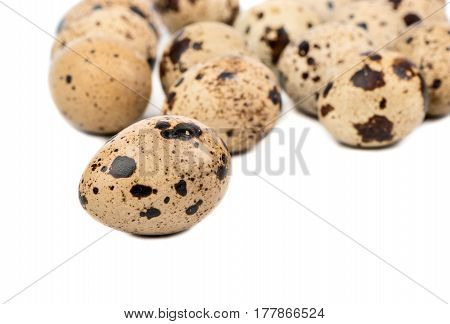 Scattered raw quail eggs on a white background