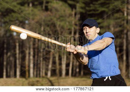 The man is shooting the ball playing baseball.