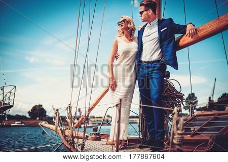 Stylish wealthy couple on a luxury yacht.