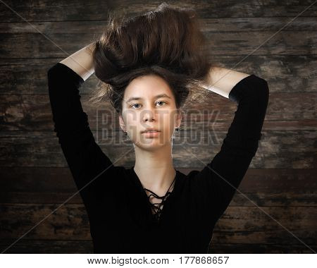 Portrait of a young girl with long hair on background of old wooden planks. Graceful sensual woman