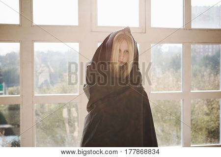 The girl with long blonde hair in dark cloth. Woman in black cloth with a piercing look. Conceptual photography. Anonymity.