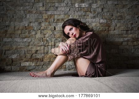 Unhappy girl pinUp with brunette hair and retro make-up with red lips in a bathrobe on a dark background. Unhappy girl sitting on the bed. Vintage image. Woman sitting pressing legs to the body. Depression