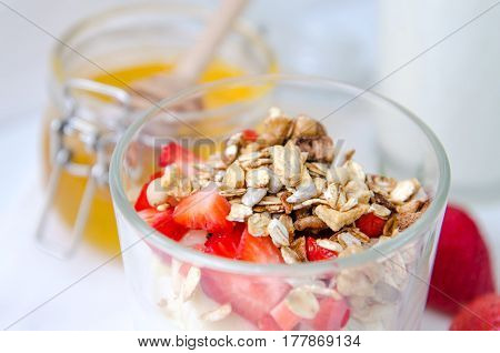 Healthy breakfast of homemade granola cereal with strawberry, nuts and fruit, honey with drizzlier on white background. Morning food, Diet, Detox, Clean Eating, Vegetarian concept.