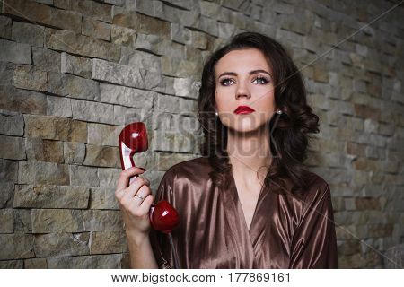 Glamour girl PinUp with brunette hair and retro make-up with red lips in a bathrobe on a dark background. Girl sitting on the bed. Vintage image. Glamour woman talking on the phone. Disk phone