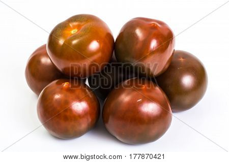 Black tomatoes Kumata on white. Studio Photo