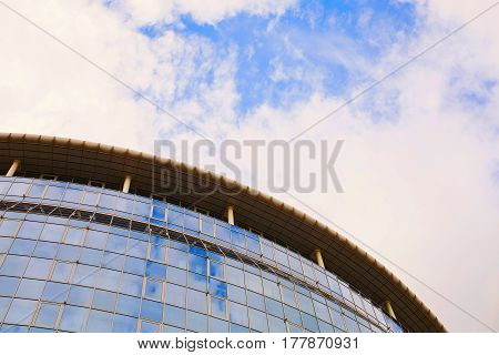 Modern building with mirrored windows with glass. Clouds in the sky. Building concept