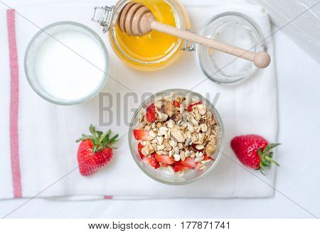 Top view healthy breakfast of homemade granola cereal with milk, strawberry, nuts and fruit, honey with drizzlier on towel, white background. Morning food, Diet, Detox, Clean Eating, Vegetarian concept.