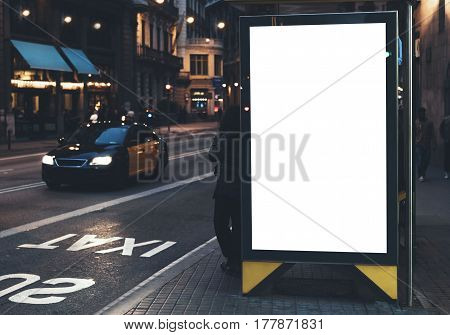 Blank advertising light box on bus stop mockup of empty ad billboard on night bus station template banner on background city street for message or text in Barcelona afisha board and headlights of taxi cars