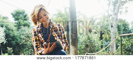 Hipster person holding in hands digital tablet with screen young girl smile reading on computer on background nature park palm landscape flare mock up technology blur female hands tourist using gadget