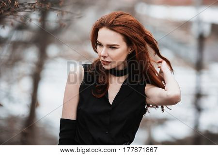 Portrait of glamorous red-haired girl with long red hair in black clothes. Red-haired woman in black dress and long black gloves posing on a background of winter autumn nature. Female street style. Beautiful elegant red-haired model