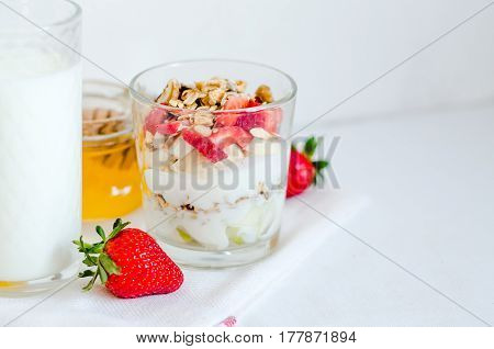 Healthy breakfast of homemade granola cereal with milk, strawberry, nuts and fruit, honey with drizzlier on towel, white background. Morning food, Diet, Detox, Clean Eating, Vegetarian concept.