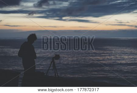 Young hipster relax beach on background ocean sunrise silhouette romantic person making photo view evening seascape photographer enjoy sunset on coast travel holidays vacation back figure on sea