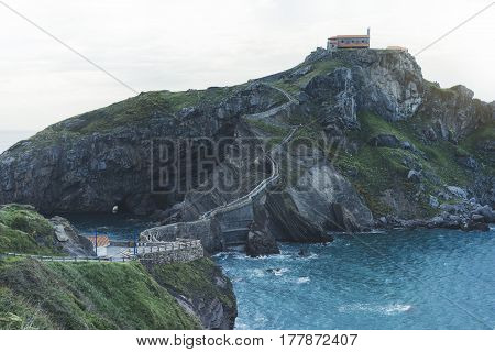 Green valley landscape on background dramatic. View sunlight blue ocean in trip holiday in basque island Gaztelugatxe. Panorama horizon of scenery foggy hills Northern Spain alps mountain. Travel mock up
